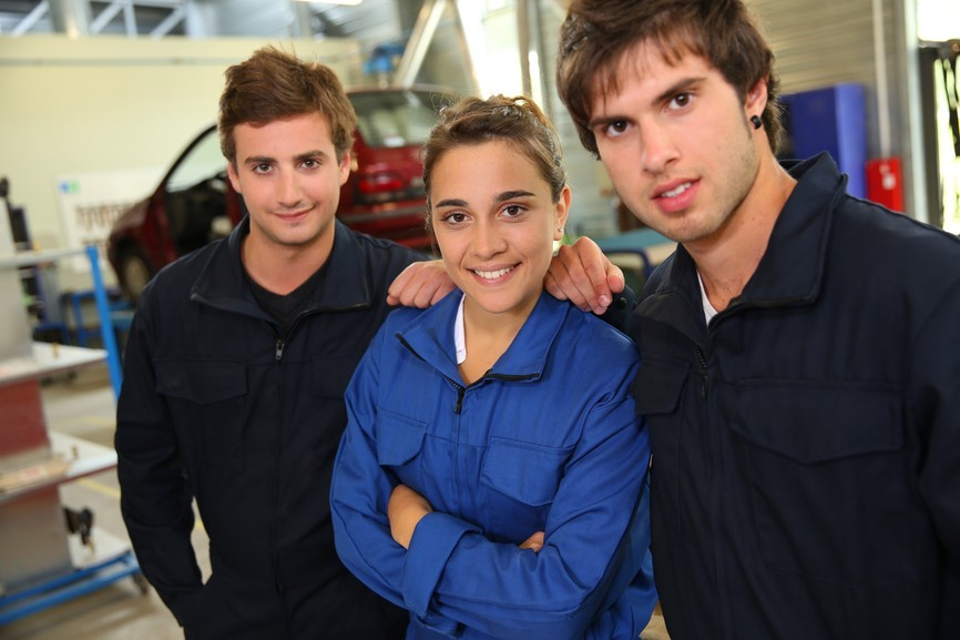 Group of students in coachbuidling standing in garage